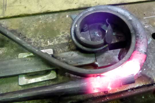 Shaping bronze door handle on a jig