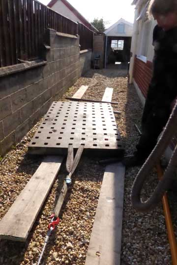 Wiching the table using scaffold poles as rollers and scaffold planks on the gravel