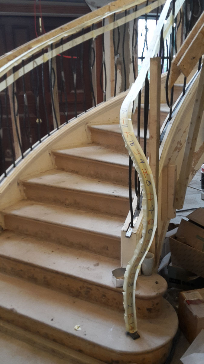 Metal handrail flows into newel post on elliptical stairs