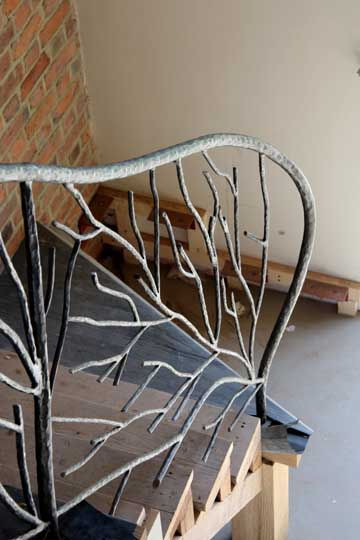 Flowing stair handrail forged steel bark texture